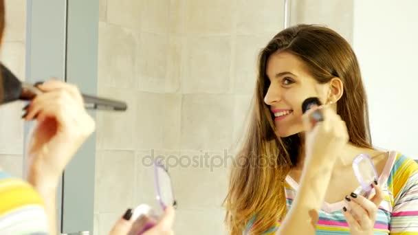 Roztomilá mladá žena před zrcadlem použití make-up pohledu kamery