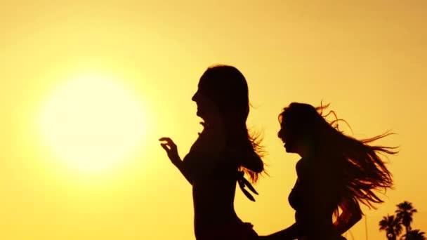 siluety dvou mladých žen v bikinách běží před sluncem na pláži při západu slunce