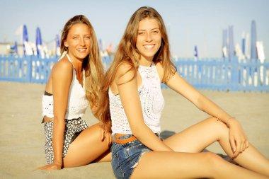Cute happy blond teenagers sitting on beach smiling looking camera