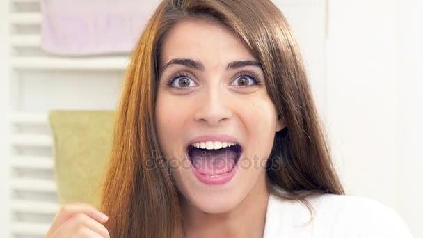 Aranyos nő mutatja gyönyörű fogak, 4 k lassított Vértes mosás után.