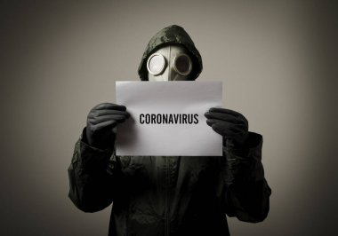 Man wearing a gas mask on his face and holding white paper with note about CORONAVIRUS. Coronavirus outbreak. COVID-19 crisis and Quarantine concept.