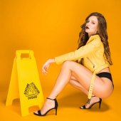 Photo sexy woman squatting near wet floor sign
