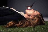 Side view of seductive woman lying on grass with golf ball in mouth