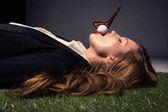 Fotografie Seitenansicht der verführerischen Frau liegt auf dem Rasen mit Golfball in Mund