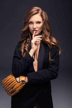 seductive woman with baseball mitt showing silence sign