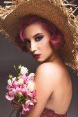 růžový vlasy dívka v slamák pózuje s květinami infront šedé pozadí
