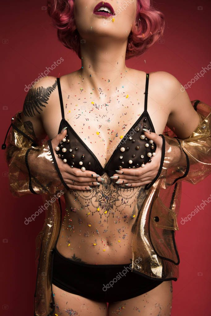 cropped image of girl with tattoos in lingerie and glaze infront of red background