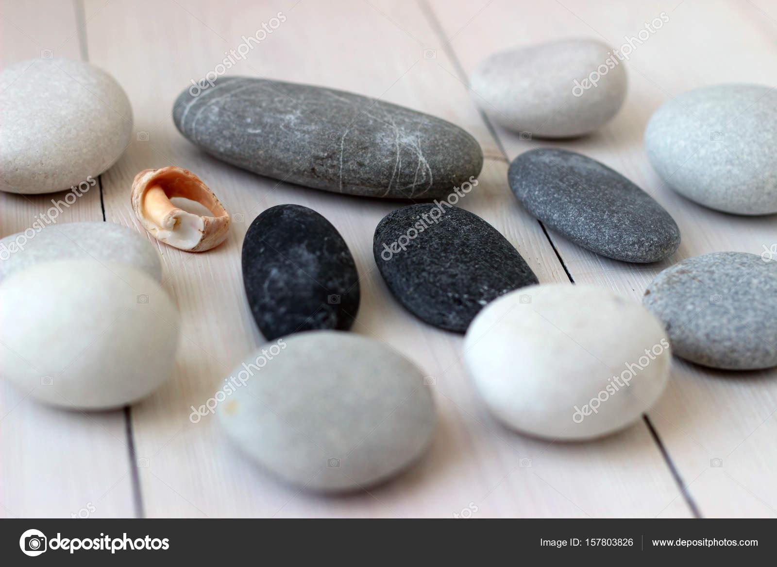 Meer-graue und weiße runde Kieselsteine auf Holztisch mit einem ...