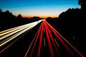 Fotografie Lange Exposition Bild von der Autobahn A2 in Deutschland Gelsenkirchen mit roten und weißen Licht Wege und ein buntes Sonnenuntergang im Hintergrund