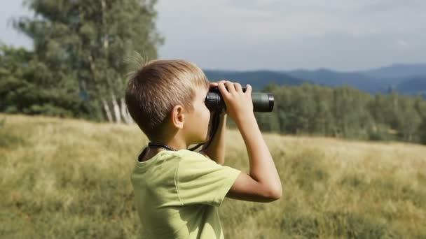 A fiú a hegy tetején áll és nézi a távcső
