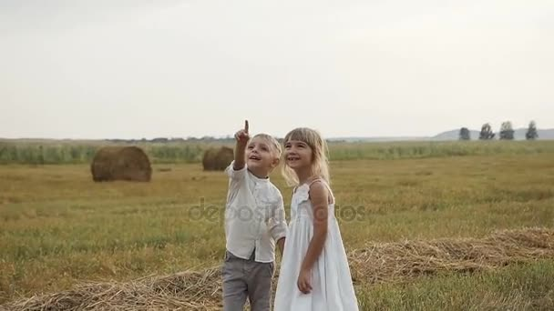 Malý chlapec s dívkou stojící v poli po dešti a při pohledu do nebe