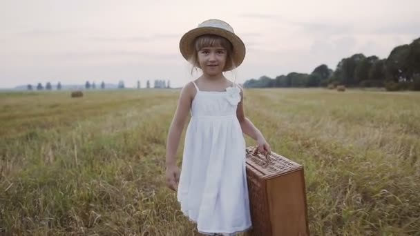 Beautiful little girl in a straw hat dressed in a white dress walks in the field and holds a straw basket in her hands