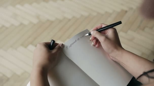 A young woman writes a note with a black pen in a notebook