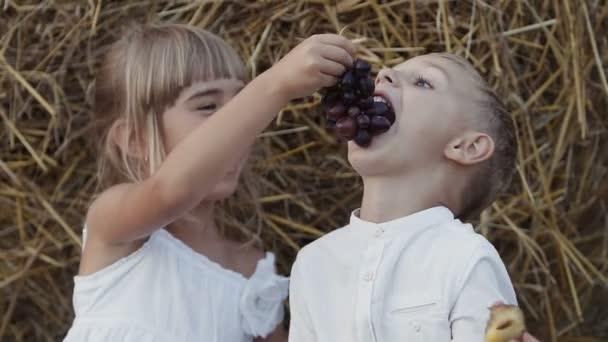 Bambina e ragazzo che mangia luva nel campo. Fortunati i bambini si siedono in un campo sotto balla di paglia. Tramonto