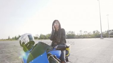 A young biker girl with dark hair in a leather jacket and sunglasses sits on her motorcycle and has fun talking on the phone