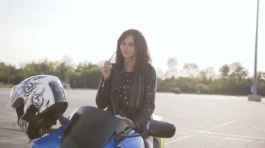 Young stylish woman sitting on her motorcycle and wearing sunglasses