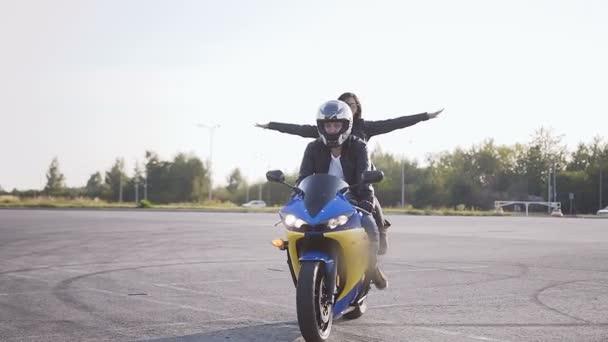 Mladý muž a mladá žena, oblečená ve stylovém oblečení bavit na motocyklu. Mladý pár motorkářů na své motorce