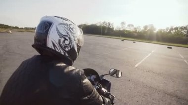 A young biker in a helmet rides on his motorcycle. Close-up