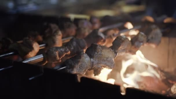 Grilled shish kebab on metal skewer.with lots of smoke. BBQ fresh beef chop slices. Flame from griil