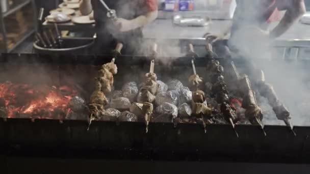 Séf keze főzés sült hús barbecue-val sok füst. Grillezett shish kebab fém nyárson