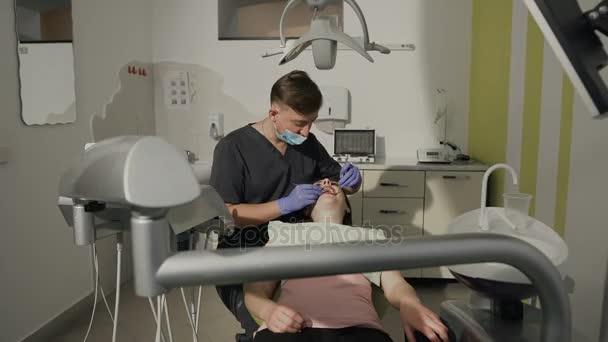 Zubař zkoumá zuby pacientů. Zdravé zuby