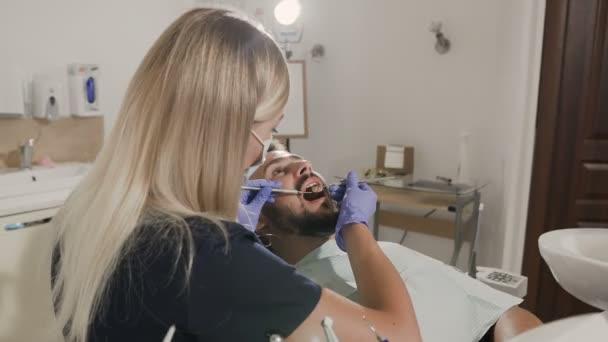 Ženské zubař léčí zuby svého pacienta