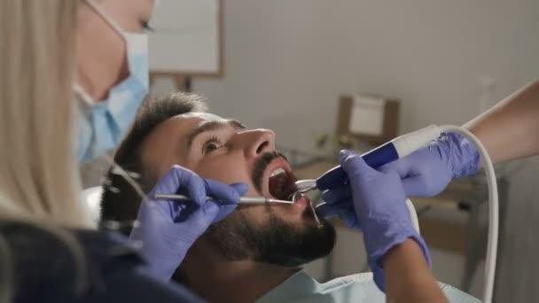 Patient having dental treatment at dentists office. Man visiting her dentist