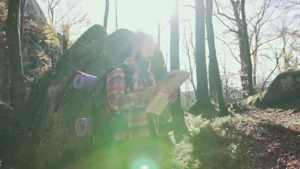Stylový bederní muž cestovatel s mapou hospodářství batoh a zkoumání na vrcholu hory, cestování koncept. Na podzim. Handsoome muž plnovous vede turistická mapa ve svých rukou