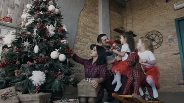 Happy family decorating Christmas tree together. Parents and two their daughters playing with Christmas presents in the living-room