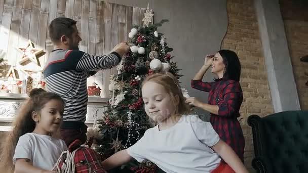Close-up. Glücklich, junge Eltern einen Weihnachtsbaum zu schmücken, und ihre Zwillingstöchter Spielzeug Reiten. Frohes neues Jahr und Weihnachten