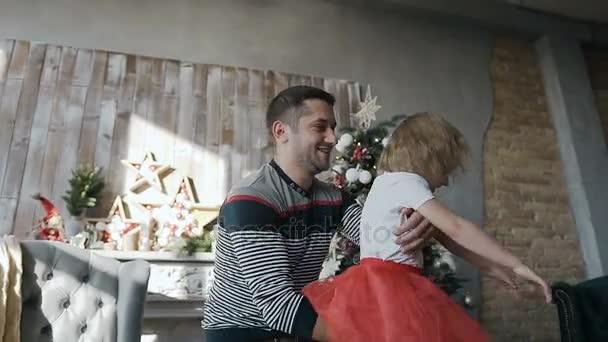 Boldog Apák is szórakoztató lánya előestéjén a karácsony karácsony a nappaliban díszes, dekoratív karácsonyfa közelében