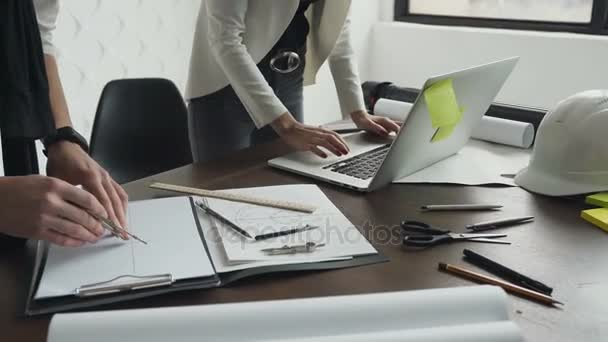 Zavřít up.Two architekti, pracující s notebookem, kompasy a výkresů pro architektonické plány
