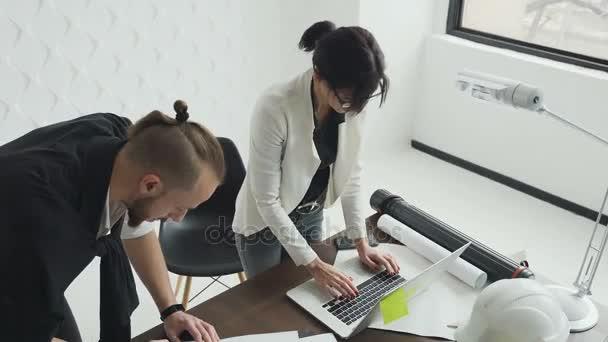 Mladá žena je architekt a designér pracující na projektu nových bytů. Vypracovat výkresy a pracovat na notebooku. Dva kolegové architektů práce v kanceláři