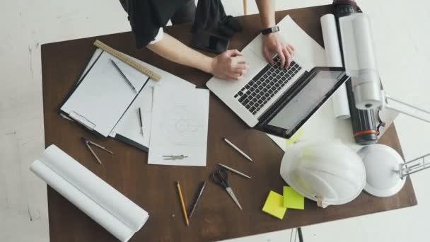 Felülnézet. Építész dolgozik a blueprint. Építészek-munkahely - építészeti projekt, tervrajz, vonalzó, ceruza, számológép, laptop, sisak, lámpa és elválasztó iránytű. Mérnöki eszközök
