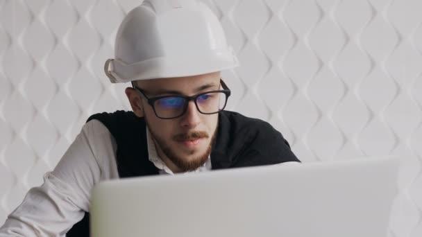 Nahaufnahme eines jungen Architekten mit Bart und Brille, der zu seiner eigenen Sicherheit einen weißen Helm trägt und an einem Laptop an einem neuen Architekturprojekt arbeitet