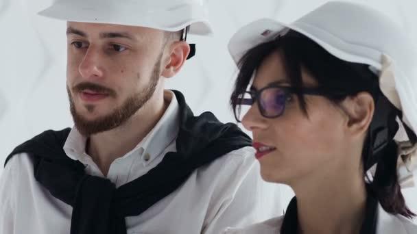Zblízka se dvou architektů v ochranné přilby spolupracovat v oblasti stavebnictví. Architekt a stavitel stojí na budování webu šetření vývoje kresby