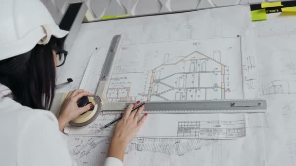 Close-up. Young female architect working on drawing device a blueprint project of new residential building. Concept of work on technical drawings
