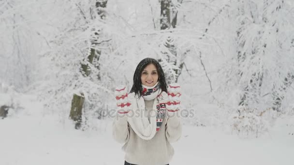 A smiling young woman with dark hair in a woolen sweater and a warm scarf is in a snow-covered forest and in woven mittens waving her hands hello