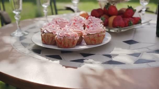 Detail. Sladké placky v růžové barvě s jahody, hrozny a mandarinky na stole. Koncept šťastný svatba. Strany sladkosti