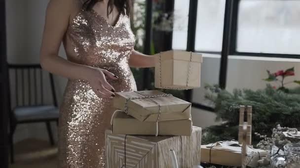 Těhotná žena dělá krabice v které zabalené dárky pro rodinu na nový rok. Početí, těhotenství. Nový rok. Vánoční svátky. Dárky
