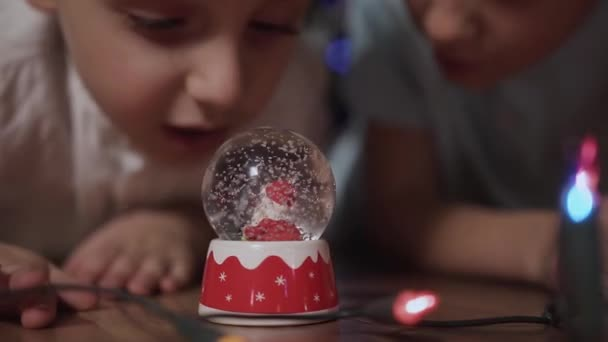 Close Up Two Children Shook The Snow Globe Put It On The Floor And