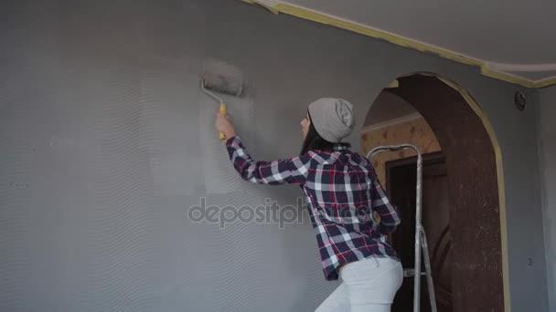 Hipster vrouw versiert haar huis schilderij van de muur in haar