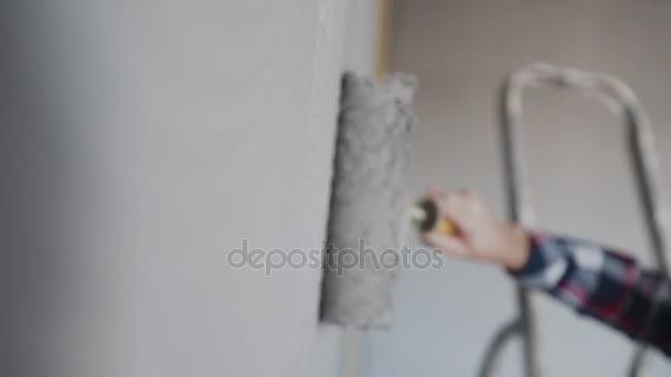 Pintar una pared desnuda con un rodillo de pintura con pintura gris ...