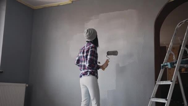 Krásná mladá dívka dělá opravy v bytě a poslouchá hudbu a tanec, Žena, která dělá nástěnné malby