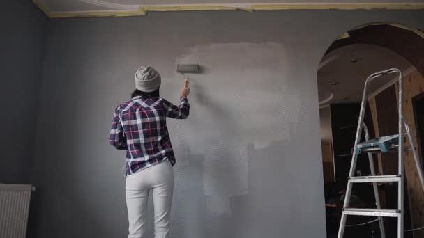 La parete della pittura ragazza con rullo in camera con una vernice grigia sta fronte quel muro e danze durante lascolto di musica in cuffia dal telefono