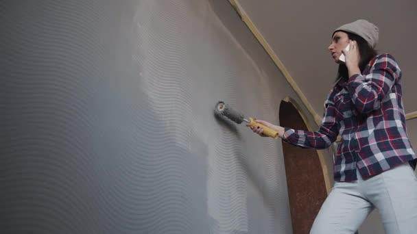 Het meisje schildert de muur in de kamer in grijs en spreekt