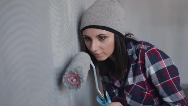 Zblízka. Mladá dívka malba stěn v šedém ložnici ve svém domě s válečkem. Malba stěn s válečkem. Malba z holé zdi s malířský váleček s šedou barvou