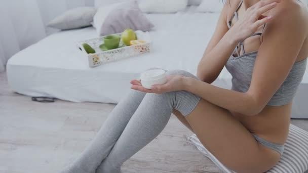 Bella bruna giovane vestita in grigio biancheria intima e calze lunghe applica la crema per il corpo a casa. Spalla e donna di nuovo corpo lozione diffusione. Cura del corpo