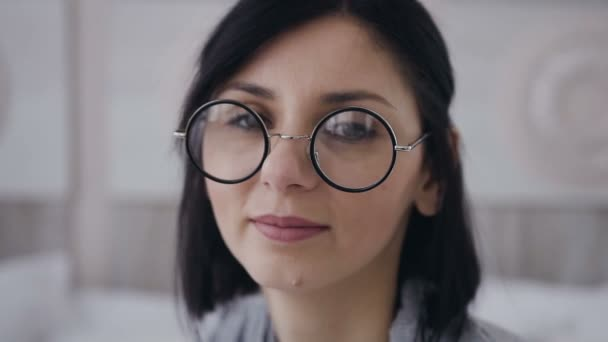 dcc1ff009f Portrait of a beautiful young brunette girl wearing round glasses the girl  smiles and looks in the camera. Indoors– stock footage