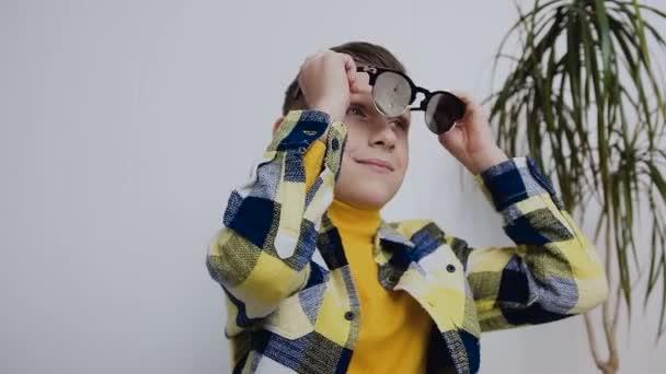 Een knappe jongen met blauwe ogen zonnebril draagt en opzij kijkt